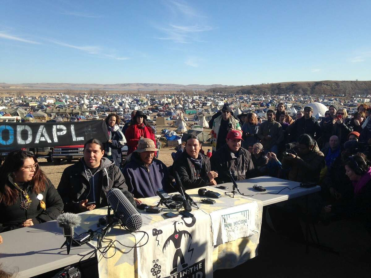 Organizers of protests against construction of the Dakota Access oil pipeline speak at a news conference on Saturday, Nov. 26, 2016, near Cannon Ball, N.D. They said they have a right to remain on land where they have been camped for months. They made the statement a day after tribal leaders received a letter from the U.S. Army Corps of Engineers, telling them the land would be closed to the public on Dec. 5. (AP Photo/James MacPherson)