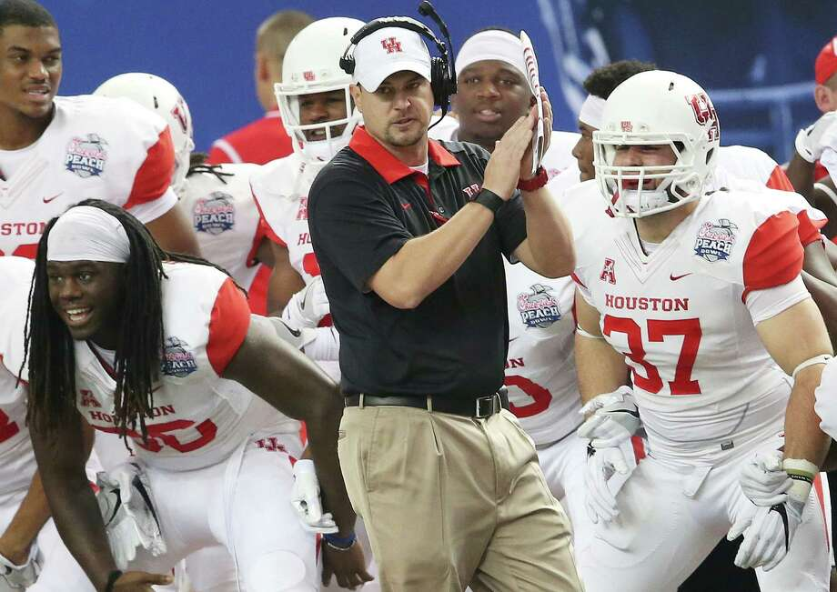 In this Dec. 31, 2015, file photo, Houston head coach Tom Herman watches play against Florida State during the first half of the Peach Bowl NCAA college football game in Atlanta. A person with direct knowledge of the discussions says Herman has told the school he is leaving to become the next coach of the Texas Longhorns. Herman would replace Charlie Strong, who was fired Saturday, Nov. 26, 2016, after three consecutive losing seasons at Texas. The person confirmed Herman's move to Texas on condition of anonymity because neither school had yet publicly announced the decision. (AP Photo/John Bazemore, File) Photo: John Bazemore, AP / Copyright 2016 The Associated Press. All rights reserved.