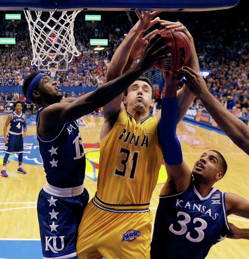 Siena's Brett Bisping (31) battles Kansas' Carlton Bragg Jr. (15) and Landen Lucas (33) for a rebound during the first half of an NCAA college basketball game Friday, Nov. 18, 2016, in Lawrence, Kan. (AP Photo/Charlie Riedel) ORG XMIT: KSCR113