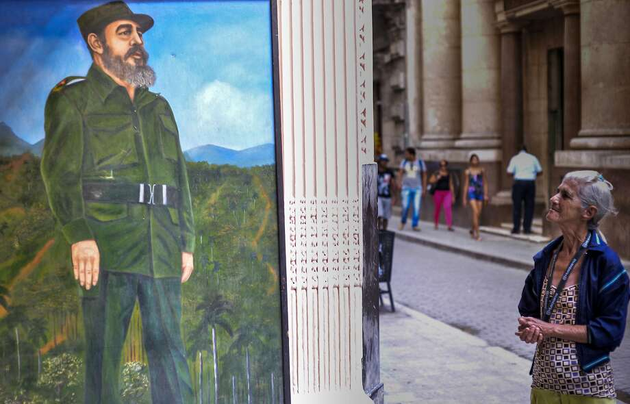 A woman pauses in Havana at a mural depicting Fidel Castro. The government has declared nine days of mourning for the former president. A mass commemoration will be held Dec. 3. Photo: ADALBERTO ROQUE, AFP/Getty Images