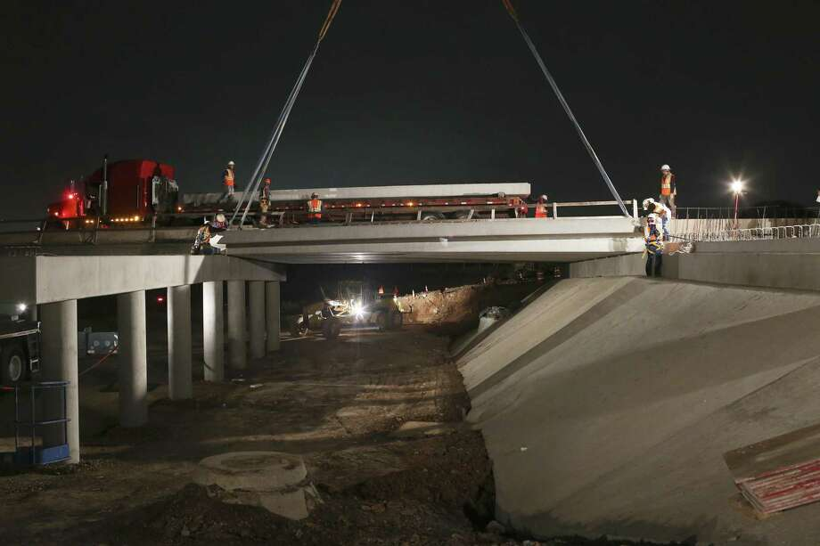 Workers place 41,000-pound beams across a span as construction continues on the bridge over French Creek along Prue Road on the city's northwest side, Tuesday, Nov. 22, 2016. The project is part of the Bexar County Flood control plan that up to date has done $500 million worth of flood control project since 2007. The plans call for a five-lane bridge over the creek that was a low-water crossing. Photo: JERRY LARA /San Antonio Express-News / © 2016 San Antonio Express-News
