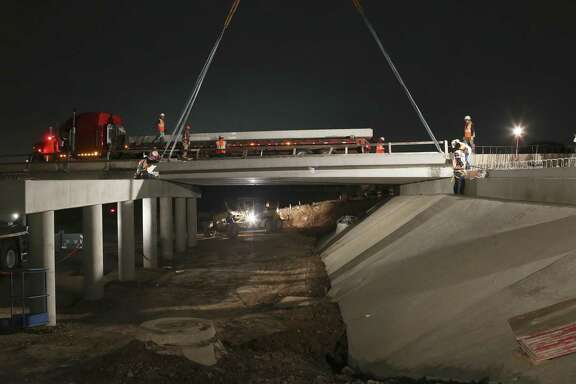 Workers place 41,000-pound beams across a span as construction continues on the bridge over French Creek along Prue Road on the city's northwest side in 2016. Impervious cover is a flood control issue, but a reader says it also contributes to man-made heat.