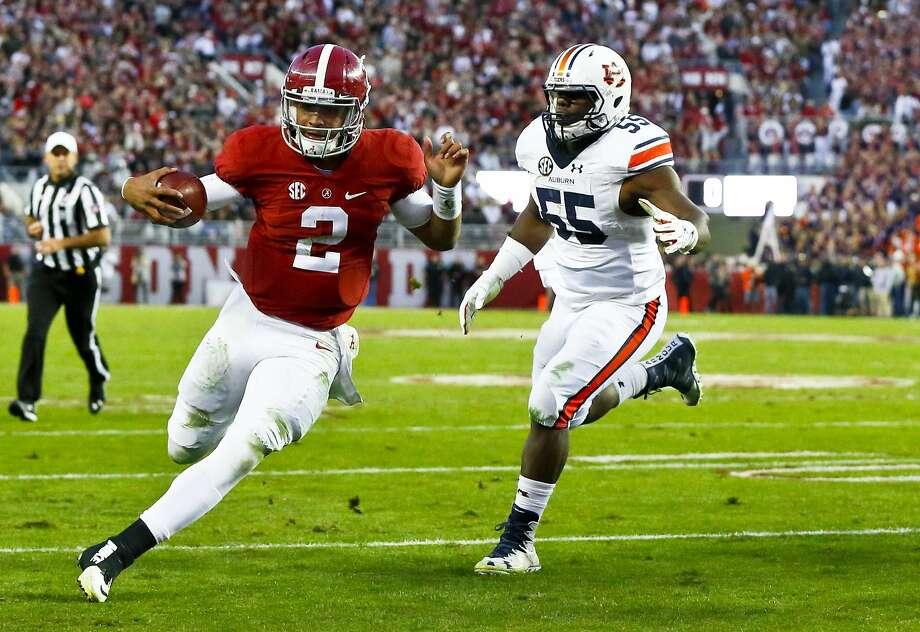 Alabama quarterback Jalen Hurts scores a touchdown against Auburn defensive lineman Carl Lawson. Photo: Butch Dill, Associated Press