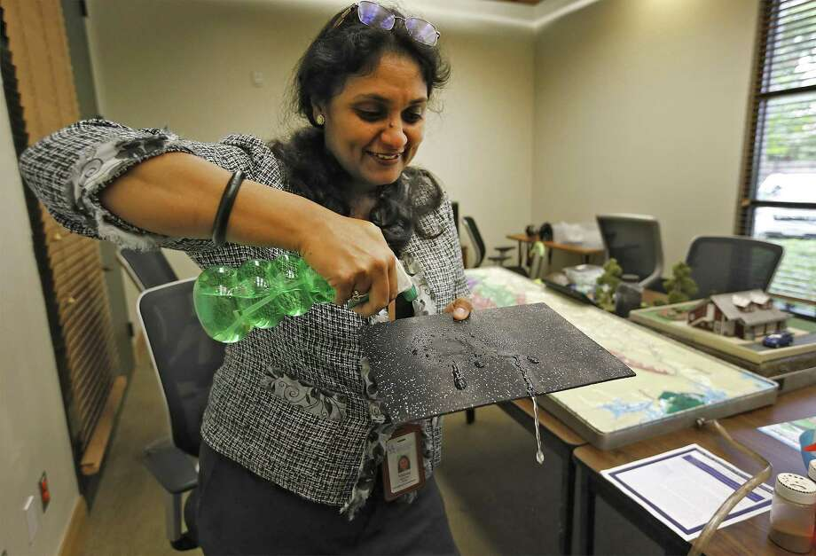 San Antonio River Authority Educational Coordinator Minna Paul shows an example of runoff from an impervious material during a demonstration of her lecture she gives to schools. Paul uses a roughly table-sized model of the watershed in an attempt to explain what happens along the river and downstream when people are not aware or conscious of their responsibilities to keeping a viable water source for the area. Another visual aid, the Low Impact Development (LID) model used by Community Relations Coordinator Clarissa Perez shows the benefits of proper ground cover as compared to impervious ground cover like pavement and concrete that can also have an effect on the local water source. The two models are used to bring about awareness and education to the public. (Kin Man Hui/San Antonio Express-News) Photo: Kin Man Hui, Staff / San Antonio Express-News / ©2016 San Antonio Express-News