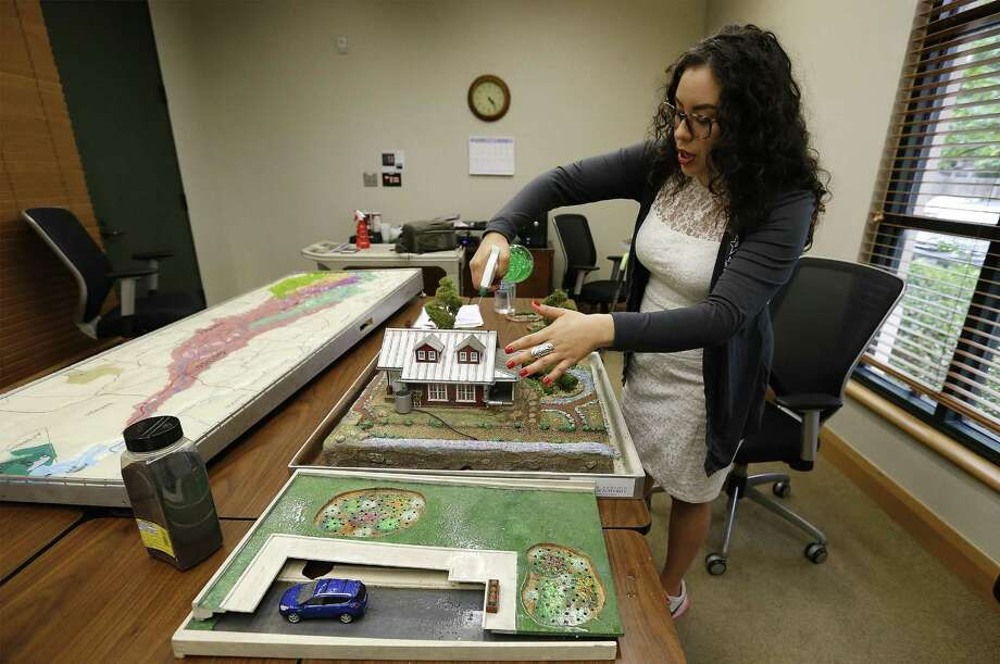 San Antonio River Authority Community Relations Coordinator Clarissa Perez used a highly detailed model called the Low Impact Development model to demonstrate to homeowners how proper ground cover and water management can better serve the home owner and the community at large as opposed to homes that have extensive impervious ground cover. The model shows that when done the right way, homes can actually improve the quality of the water that enters the San Antonio River and water table. (Kin Man Hui/San Antonio Express-News) Photo: Kin Man Hui, Staff / San Antonio Express-News / ©2016 San Antonio Express-News