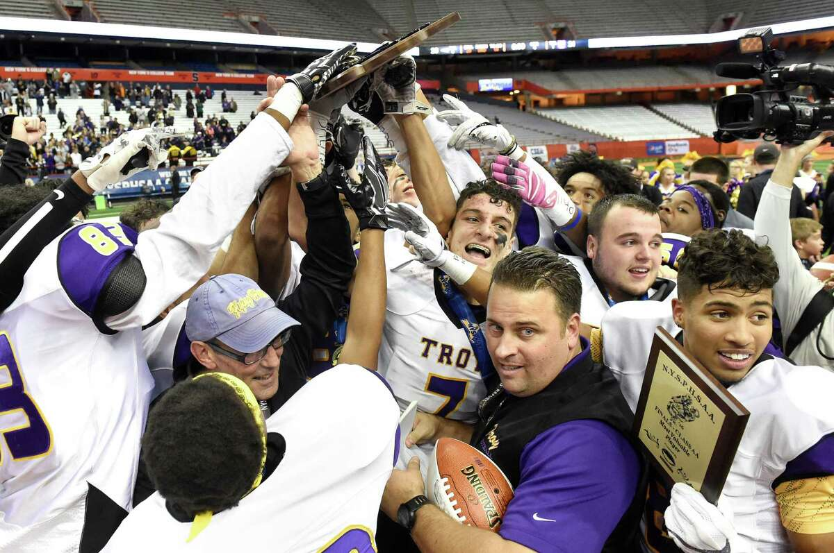 Troy hoists the first-place plaque as they celebrate their 21-20 win over Victor in the Class AA state football final on Saturday, Nov 26, 2016, at the Carrier Dome in Syracuse, N.Y. (Cindy Schultz / Times Union)