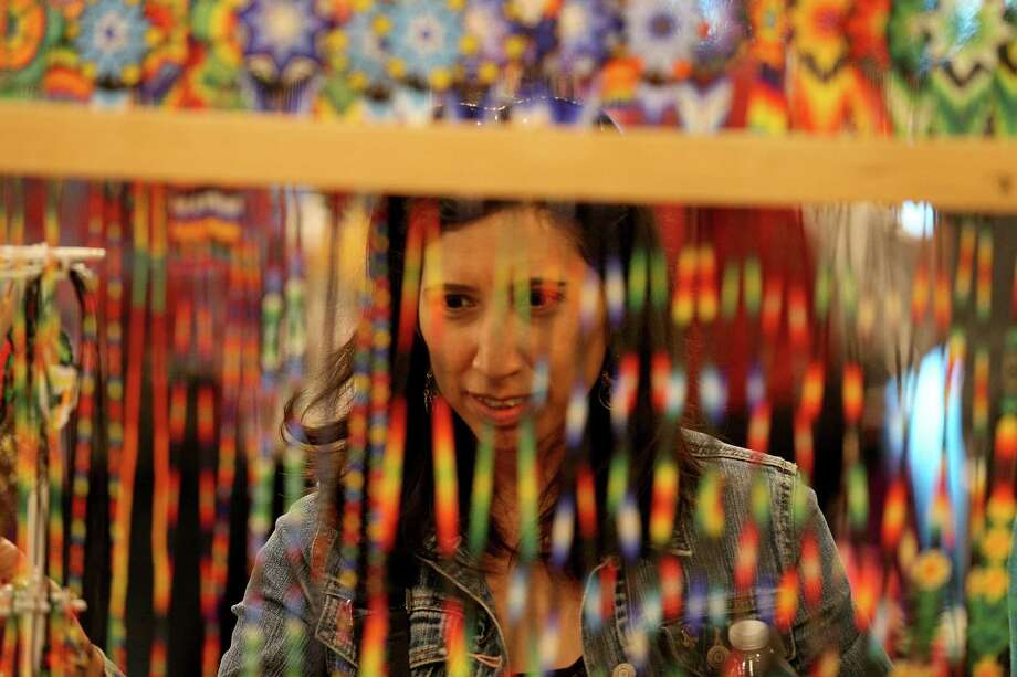 Susan Castro looks at handmade necklaces at the International Peace Market, put on by the Esperanza Peace & Justice Center. Photo: Photos By Edward A. Ornelas /San Antonio Express-News / © 2016 San Antonio Express-News