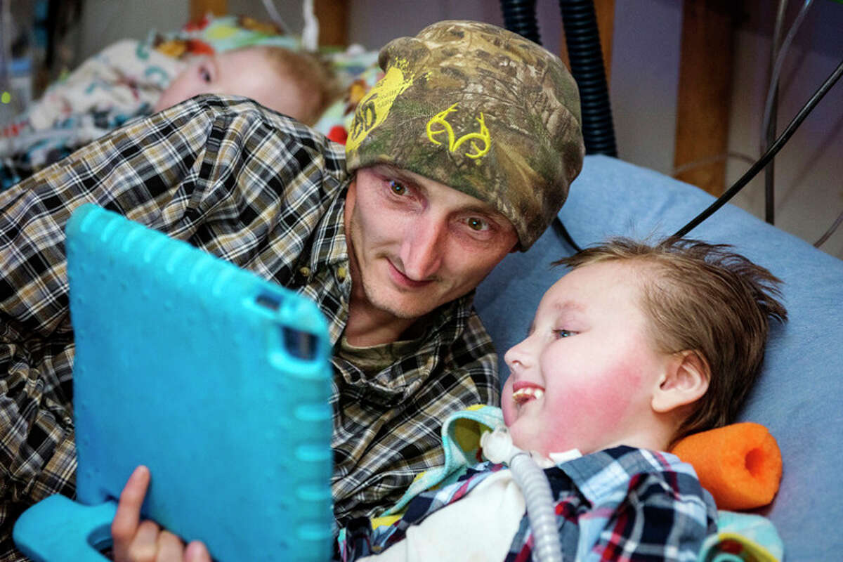 DANIELLE McGREW TENBUSCH | for the Daily News Les Snyder watches YouTube videos with his son, Logan Snyder, 4, at their home in Wheeler on Wednesday. Logan and his 2-year-old brother, Noah, were diagnosed with spinal muscular atrophy, a rare deadly degenerative disease.