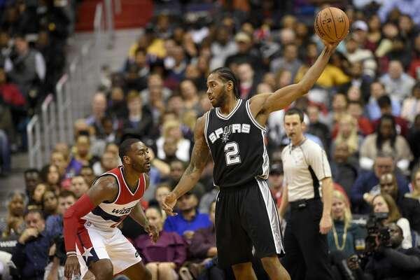 San Antonio Spurs forward Kawhi Leonard (2) holds the ball against Washington Wizards guard John Wall (2) during the first half of an NBA basketball game, Saturday, Nov. 26, 2016, in Washington. (AP Photo/Nick Wass)
