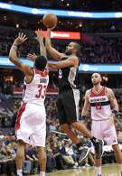 San Antonio Spurs guard Tony Parker, of France, (9) goes to the basket against Washington Wizards guard Trey Burke (33) and center Marcin Gortat, of Poland, (13) during the second half of an NBA basketball game, Saturday, Nov. 26, 2016, in Washington. The Spurs won 112-100. (AP Photo/Nick Wass)
