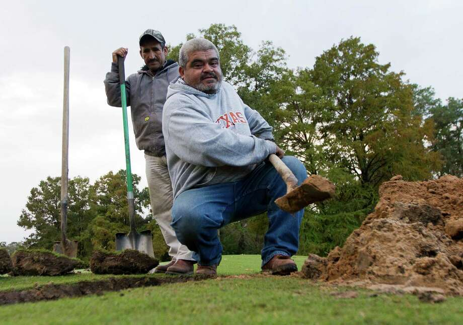 Carlos Malen, right, works to dig out a sprinkler as Juan Bantes looks on at The Village Golf Club Wednesday, Nov. 23, 2016, in Panorama Village. The golf club plans to replace the sprinkler system to more efficiently water sections of the course. Photo: Jason Fochtman, Staff Photographer / Houston Chronicle
