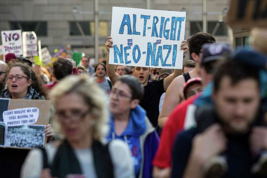 "Demonstrators march to the site of the annual ""Become Who We Are"" conference, a key gathering of the self-declared ""alt-right"" movement, on Nov. 19 in Washington. Photo: AL DRAGO, STR / NYTNS"