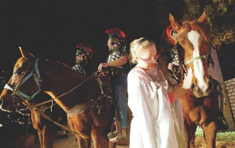 Haley Hitchcock pets a horse as actors and actress get into place for a group photo during a rehearsal for Bethlehem City at West Conroe Baptist Church Dec. 2, 2015. Photo: File Photo / Conroe Courier / HCN