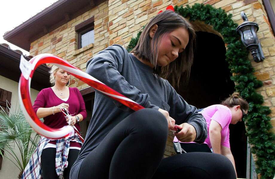 Ashlyn Berry helps employees with Texas Children's Hospital decorate a home at MainStreet America Tuesday, Nov. 22, 2016, in Spring. Texas Children's, in addition to nine other non-profit organizations, decorated homes on the property in hopes of winning a $10,000 prize. Visitors to MainStreet's 'Christmas on MainStreet' event can donate money to each organization. The group with the most money raised will win the prize. The event runs every Saturday from 6 p.m. to 9 p.m. starting Nov. 26 and running though Dec. 17. Photo: Jason Fochtman, Staff Photographer / Houston Chronicle