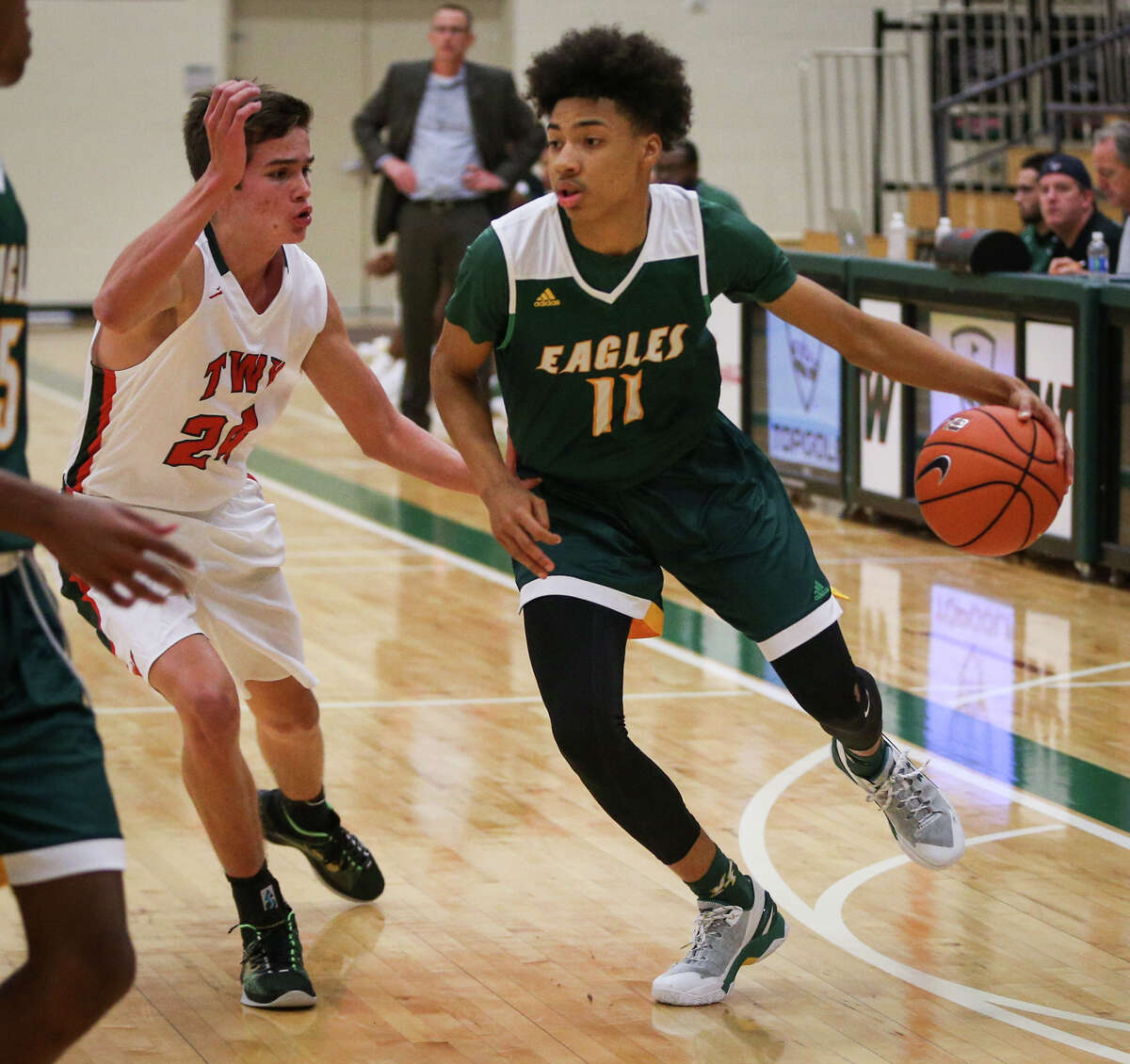 Klein Forest's Durey Cadwell (11) drives for the basket as The Woodlands' Gabe Carbajal (24) defends during the varsity boys basketball game on Saturday, Nov. 26, 2016, at The Woodlands High School. (Michael Minasi / Chronicle)