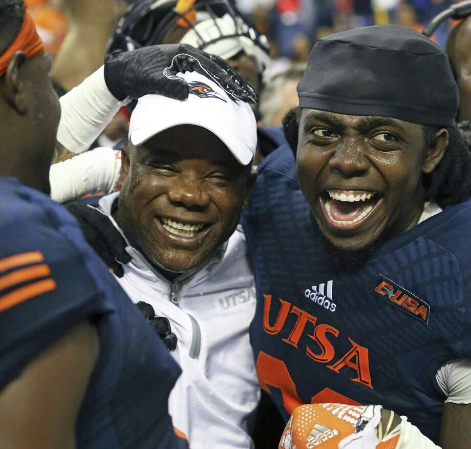 Andrew King (right) and other players swarm around coach Frank Wilson after UTSA beat Charlotte at the Alamodome to make itself bowl eligible on Nov. 26, 2016. Photo: Tom Reel /San Antonio Express-News / 2016 SAN ANTONIO EXPRESS-NEWS