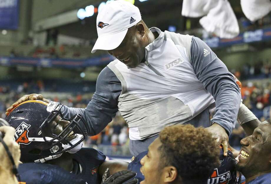 T.J. King gets a pat on the helmet as players hoist UTSA coach Frank Wilson and enjoy the bowl-bid-clinching victory over Charlotte at the Alamodome on Nov. 26, 2016. Photo: Tom Reel /San Antonio Express-News / 2016 SAN ANTONIO EXPRESS-NEWS