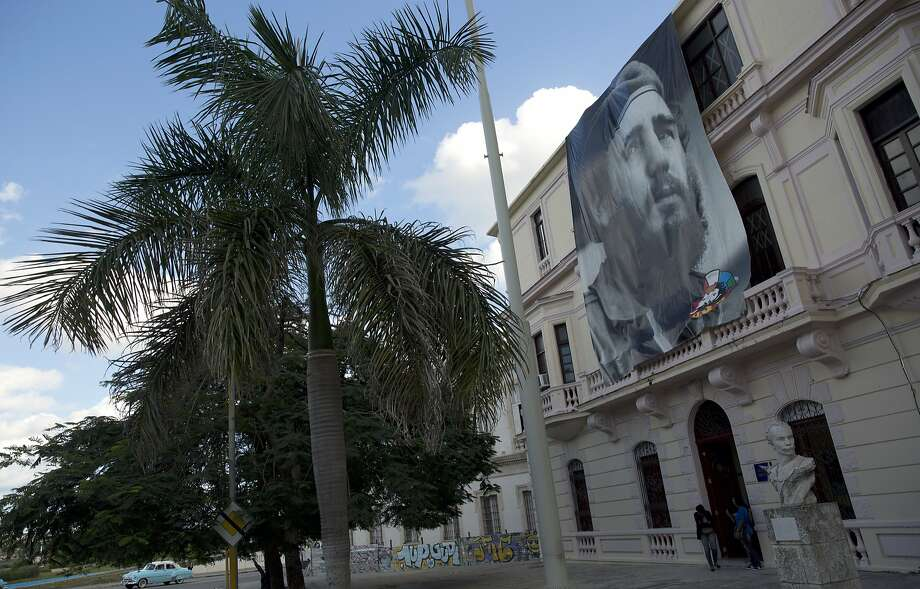 A large photograph of the late Fidel Castro hangs on the Young Communists Party headquarters, above a bust of independence hero Jose Marti in Havana, Cuba, Sunday, Nov. 27, 2016. Cuba will observe nine days of mourning for the former president who ruled Cuba for half a century. (AP Photo/Enric Marti) Photo: Enric Marti, Associated Press