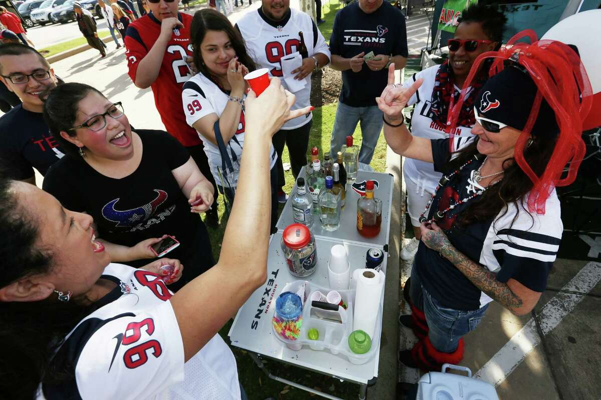 Houston Texans fan Elizabeth Perez, left, from Chicago, cheers with local Texans fans with a shot of fireball at the NRG Stadium parking lot before the team takes on San Diego Chargers Sunday, Nov. 27, 2016, in Houston. Perez has been a Texans fan for about 10 years and Sunday was her first time watching a Texans game.