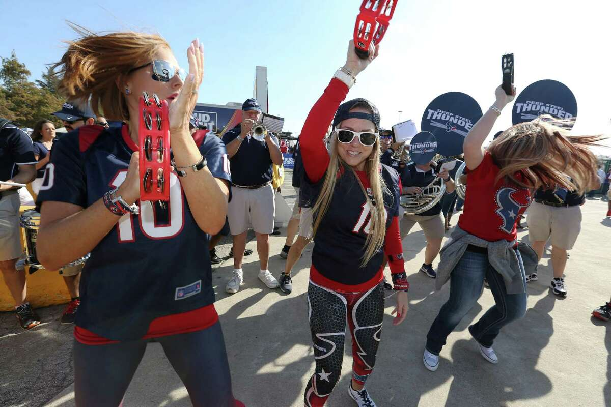 Houston Texans fans Regan Dunaway, left, Ashley Henderson and Candi Edmonston dance along with Deep Steel Thunder band's music at the NRG Stadium parking lot before the team takes on San Diego Chargers Sunday, Nov. 27, 2016, in Houston.