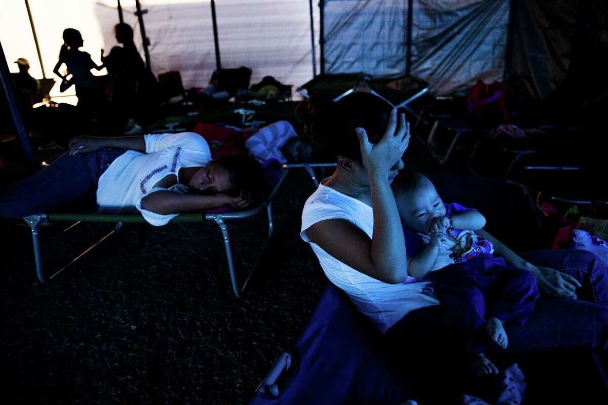 Gabriella Medina holds her four-month-old son, Selvin Eduardo Albarado, on a cot in a temporary shelter at Sacred Heart Catholic Church Tuesday, Nov. 15, 2016 in McAllen. The church assists hundreds of immigrants everyday who arrive in McAllen after being processed by U.S. Border Patrol by giving them food, clothing and a place to sleep if necessary. ( Michael Ciaglo / Houston Chronicle )