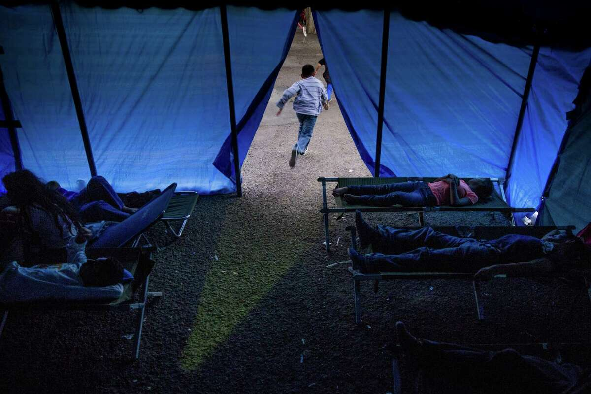 Kids run out of a temporary shelter as other immigrants, most of whom are escaping violence and poverty in El Salvador, Honduras and Guatemala, claim cots to spend the night at Sacred Heart Catholic Church Tuesday, Nov. 15, 2016 in McAllen. The church assists hundreds of immigrants everyday who arrive in McAllen after crossing the border by giving them food, clothing and a place to sleep if necessary. ( Michael Ciaglo / Houston Chronicle )