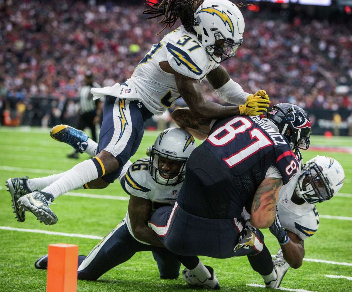 San Diego Chargers strong safety Jahleel Addae (37) and cornerback Casey Hayward (26) stop Houston Texans tight end C.J. Fiedorowicz (87) short of the goal line on third down during the fourth quarter of an NFL football game at NRG Stadium on Sunday, Nov. 27, 2016, in Houston. The Texans kicked a field goal on the next play.