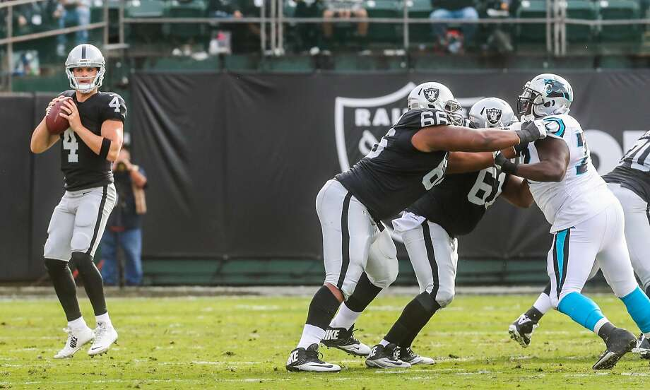 Quarternack Derek Carr (left, #4) prepares to make a pass as his offensive lineman Gabe Jackson (#66) and Rodney Hudson (#61) block for him, in the first half of the game against the Carolina Panthers, at the Oakland Colliseum, in Oakland, California, on Sunday, Nov. 27, 2016. Photo: Gabrielle Lurie, The Chronicle