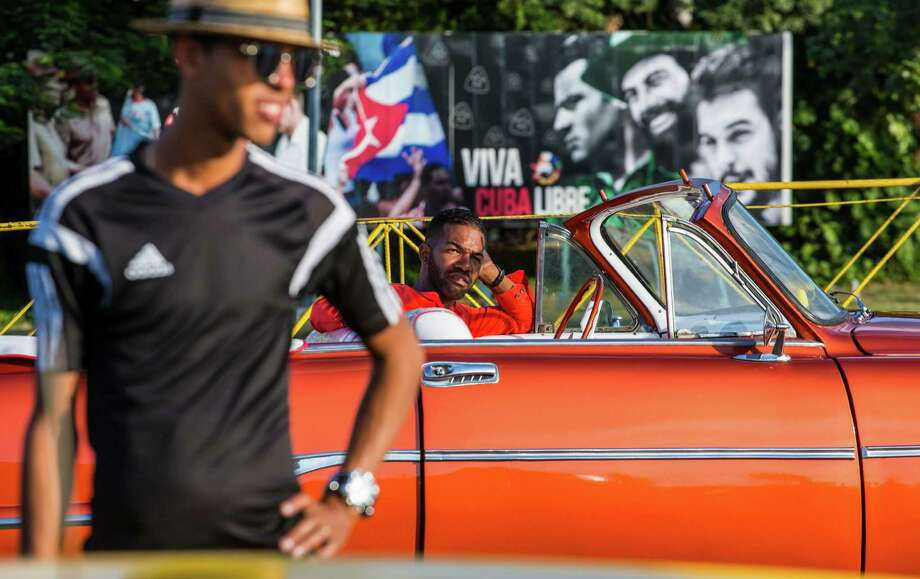 Drivers wait for tourists, in vintage American convertibles at Revolution Square in Havana, Cuba, Sunday, Nov. 27, 2016. Cuba's government declared nine days of national mourning after Cuban leader Fidel Castro died Friday and this normally vibrant city has been notably subdued. As Cuba prepares a massive commemoration for Castro, tens of thousands of high-season travelers have found themselves accidental witnesses to history and in the middle of a somber city that's little like its usual exuberant self. Photo: Desmond Boylan, AP / Copyright 2016 The Associated Press. All rights reserved.