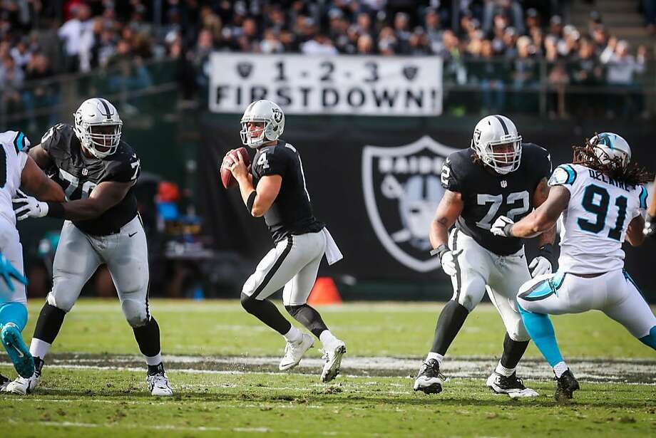 Quarternack Derek Carr (left, #4) prepares to make a pass as his offensive lineman Kelechi Osemele (left, #70) and Donald Penn (right, #72) block for him, in the first half of the game against the Carolina Panthers, at the Oakland Colliseum, in Oakland, California, on Sunday, Nov. 27, 2016. Photo: Gabrielle Lurie / The Chronicle