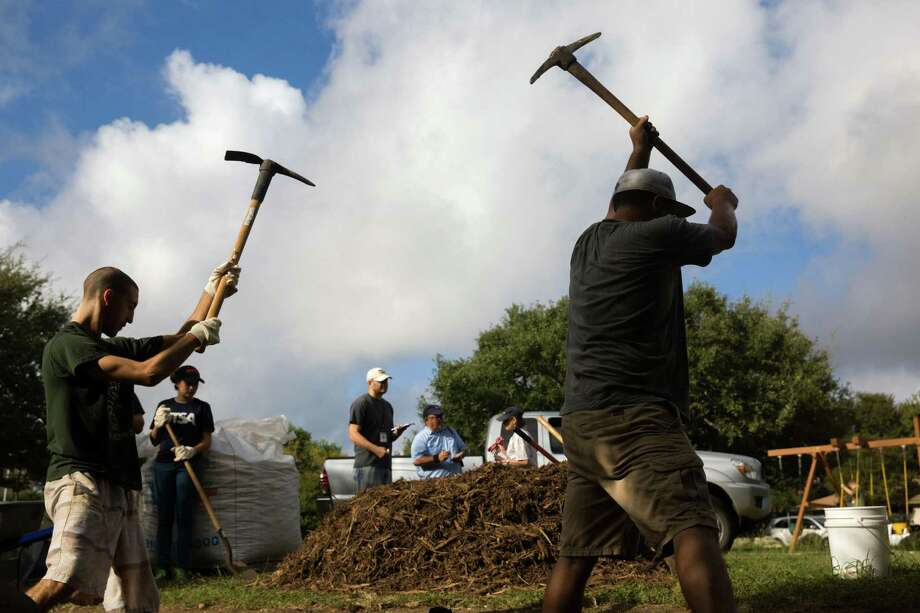 Forrest Wilkinson (left) and David Lowak use pickaxes in September to dig a hole at the Woods of Shavano for a rain garden aimed at retaining stormwater and reducing pollutants that reach the Edwards Aquifer. Photo: Ray Whitehouse /For The San Antonio Express-News