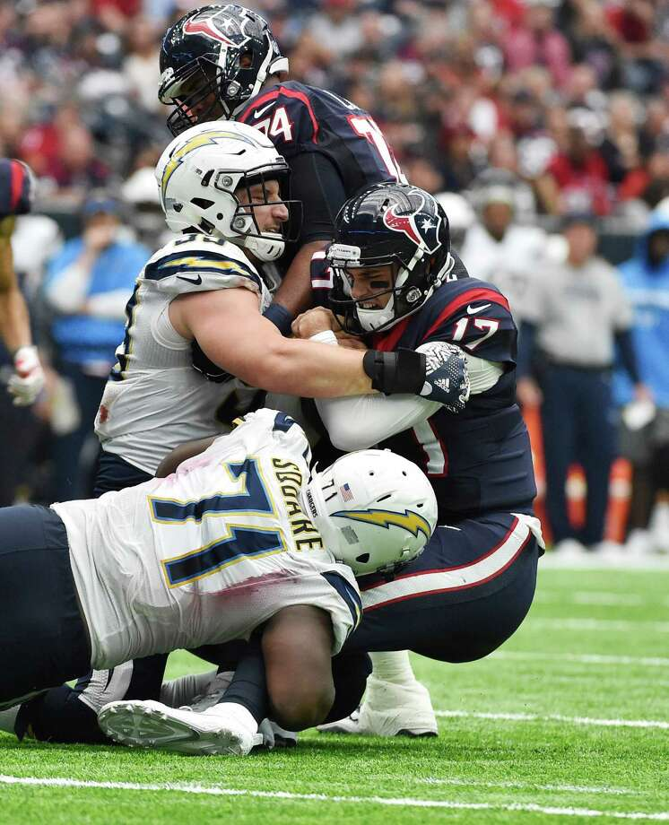 Houston Texans quarterback Brock Osweiler (17) is sacked by San Diego Chargers' Joey Bosa, left, and Damion Square (71) during the first half of an NFL football game Sunday in Houston. Photo: Eric Christian Smith, Associated Press / FR171023 AP