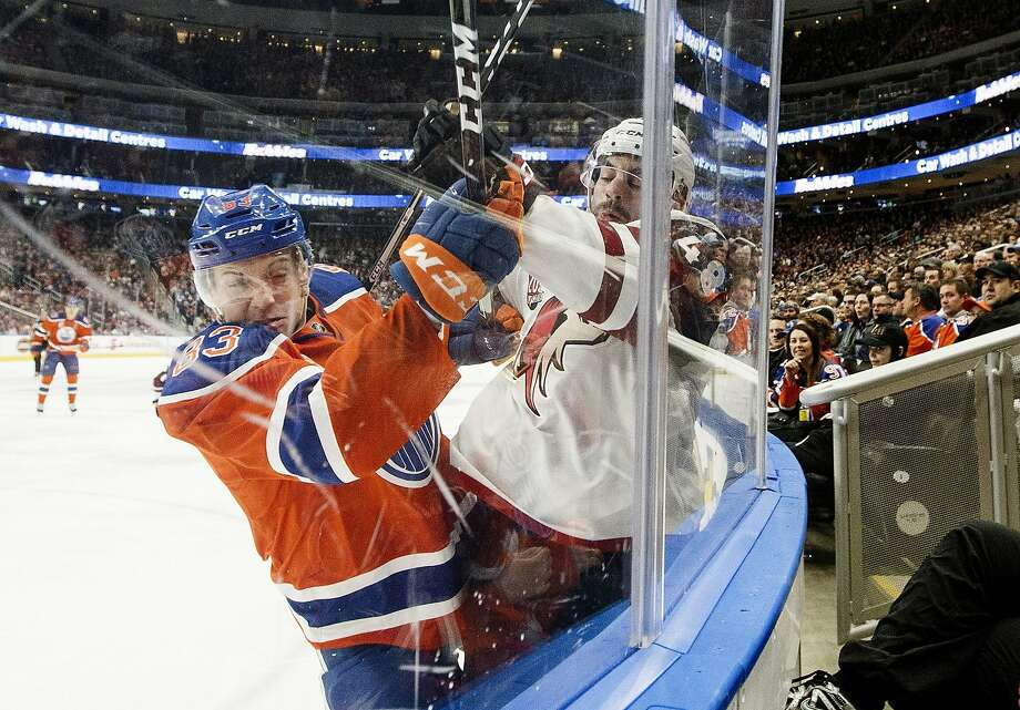 Arizona's Jordan Martinook is checked into the boards by Edmonton's Matthew Benning in the first period. Photo: JASON FRANSON, Associated Press