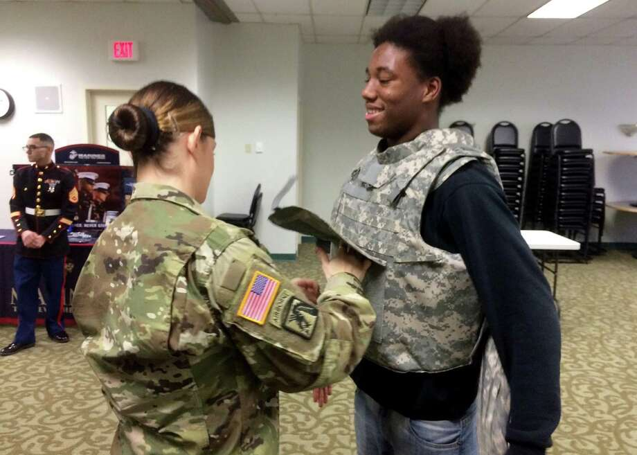 Michael McCagg / BOCES Career and Technical School New York National Guard Sgt. Ami Vernon helps Capital Region BOCES Career and Technical (CTE) School building trades student Naseem Kimble of Schenectady put on a flak vest during military career day at the Albany CTE campus.