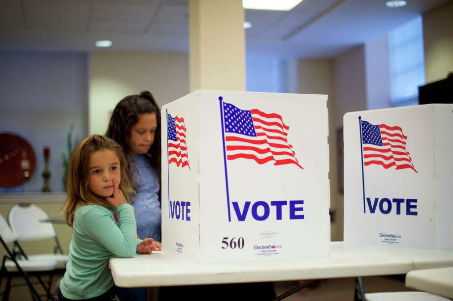 FILE -- Angelina Blewitt, 5, left, and her sister, Mackayla, 9, as their mother, Bridget, votes in Spring City, Pa., Nov. 8, 2016. Weeks after Hillary Clinton conceded the election, impassioned supporters are urging her to challenge the results in three states decided by the thinnest of margins, grasping at the last straws to reverse Donald Trump's decisive majority in the Electoral College. (Mark Makela/The New York Times) ORG XMIT: XNYT118 Photo: MARK MAKELA / NYTNS
