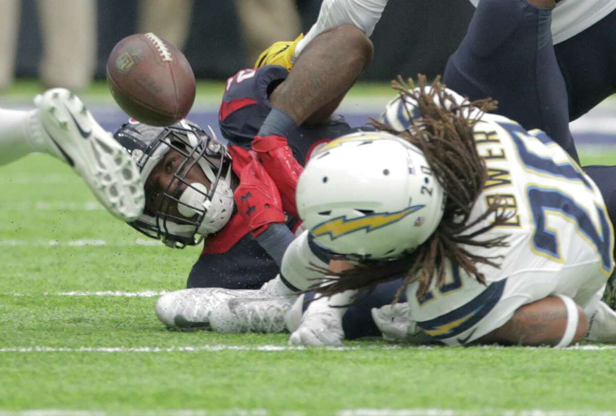 Houston Texans running back Lamar Miller (26) fumble the ball after hitting San Diego Chargers free safety Dwight Lowery (20) on Sunday, Nov. 27, 2016, in Houston. The initial ruling is that he was down, but was overturned when San Diego Chargers challenged it.
