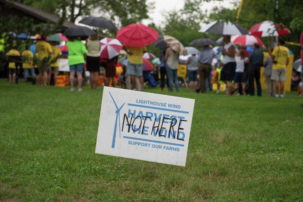FILE - In this Aug. 25, 2016 file photo, people gather to protest the installation of windmills in Somerset, N.Y. A battle of clean energy vs. the environment is playing out in western New York over a plan to build dozens of wind turbines that could be among the nation?'s tallest, rising 600 feet above the scenic shores of Lake Ontario. (Joed Viera/The Union-Sun & Journal via AP, File) ORG XMIT: NYLOC501