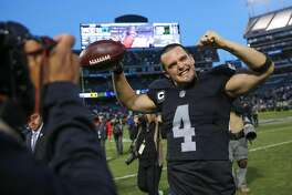 Oakland Raiders quarterback Derek Carr, #4, waves to the crowd at the end of a game against the Carolina Panthers which ended in a Raiders victory, of 35-32,  at the Oakland Colliseum, in Oakland, California, on Sunday November 27, 2016. Carr wears a glove over his right hand after injuring a finger during the game.