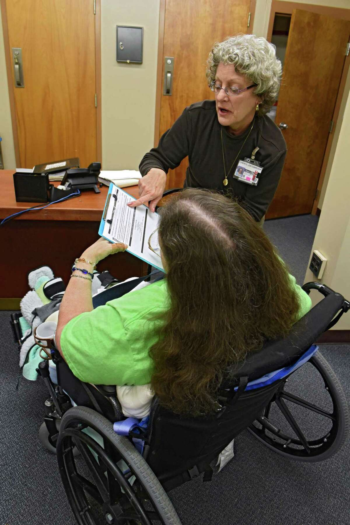 Social worker Cheryl Estabrook, standing, helps a resident at the Albany County Nursing Home on Monday, Nov. 21, 2016 in Colonie, N.Y. (Lori Van Buren / Times Union)