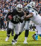 Oakland Raiders player Jamize Olawale (#49, left) carries the ball down the field during a game against the Carolina Panthers which ended in a Raiders victory, of 35-32,  at the Oakland Colliseum, in Oakland, California, on Sunday November 27, 2016.