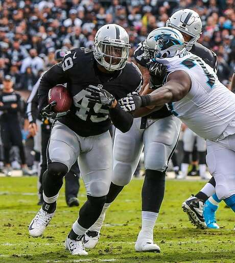 Oakland Raiders player Jamize Olawale (#49, left) carries the ball down the field during a game against the Carolina Panthers which ended in a Raiders victory, of 35-32,  at the Oakland Colliseum, in Oakland, California, on Sunday November 27, 2016. Photo: Gabrielle Lurie, The Chronicle