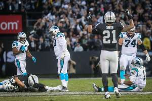 Oakland Raiders player Khalil Mack, #52 (bottom, left) is seen clutching the ball after knocking it out of Carolina Panthers quarterback Cam Newton's, #1 (right), hands, during the final seconds of a game which ended in a Raiders victory, of 35-32,  at the Oakland Colliseum, in Oakland, California, on Sunday November 27, 2016.