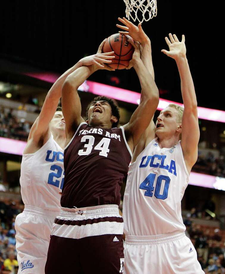Texas A&M's Tyler Davis, center, is defended by UCLA's Thomas Welsh, left, and TJ Leaf during the first half of an NCAA college basketball game in the Wooden Legacy tournament Sunday in Anaheim, Calif. Photo: Jae C. Hong, Associated Press / Copyright 2016 The Associated Press. All rights reserved.