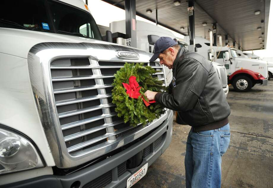Wreaths Across America founder Morrill Worcester, of Columbia Falls, Maine, affixes a balsam wreath to a truck's grill at the Pilot Travel Center truckstop in Milford, Conn. on Tuesday, November 26, 2013. One half of a Trucking's Patriot Pair, the wreath is meant to act as a rolling tribute to military veteran's while a matching wreath will be laid on a veteran's gravesite at Arlington National Cemetary in Virginia on December 14. Photo: Brian A. Pounds / Brian A. Pounds / Connecticut Post