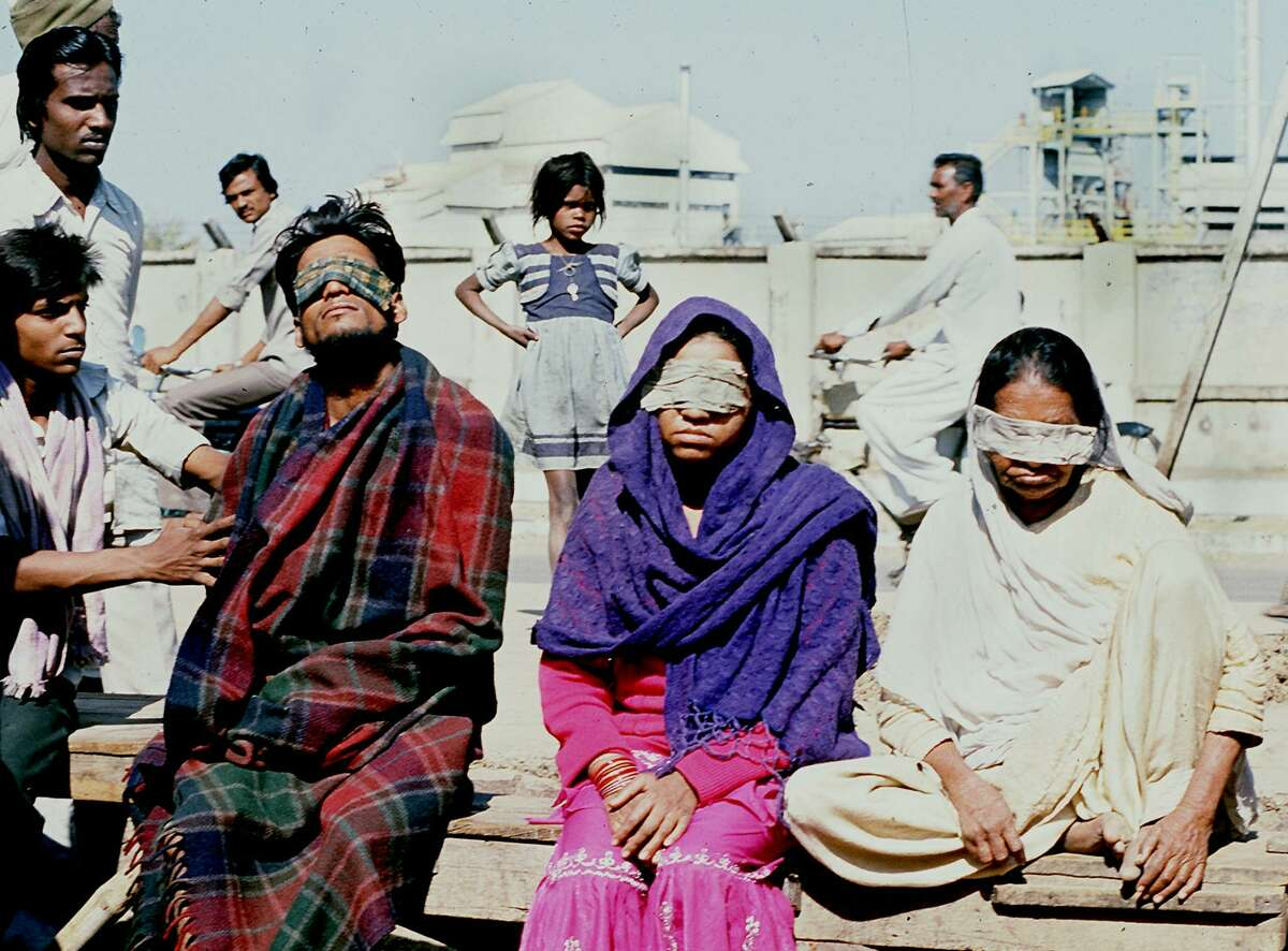 BHOPAL, INDIA: A December 1984 file photo shows victims who lost sight after poison gas leak from a pesticides plant in the central Indian city of Bhopal squating in front of the US Union Carbide factory (Shown in background). The December 1984 gas leak was the world's worst industrial disaster which claimed more than 2,850 lives. = INDIA TODAY = AFP PHOTO (Photo credit should read AFP/Getty Images)