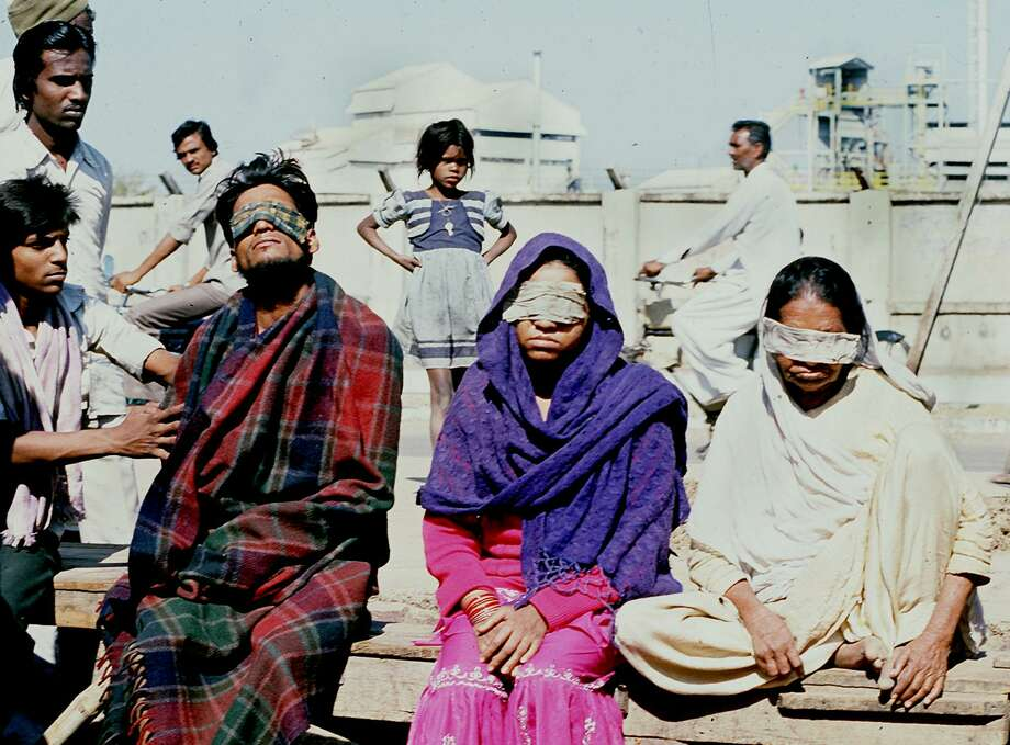 BHOPAL, INDIA:  A December 1984 file photo shows victims who lost sight after poison gas leak from a pesticides plant in the central Indian city of Bhopal squating in front of the US Union Carbide factory (Shown in background). The December 1984 gas leak was the world's worst industrial disaster which claimed more than 2,850 lives.   = INDIA TODAY = AFP PHOTO (Photo credit should read AFP/Getty Images) Photo: -/AFP/Getty Images