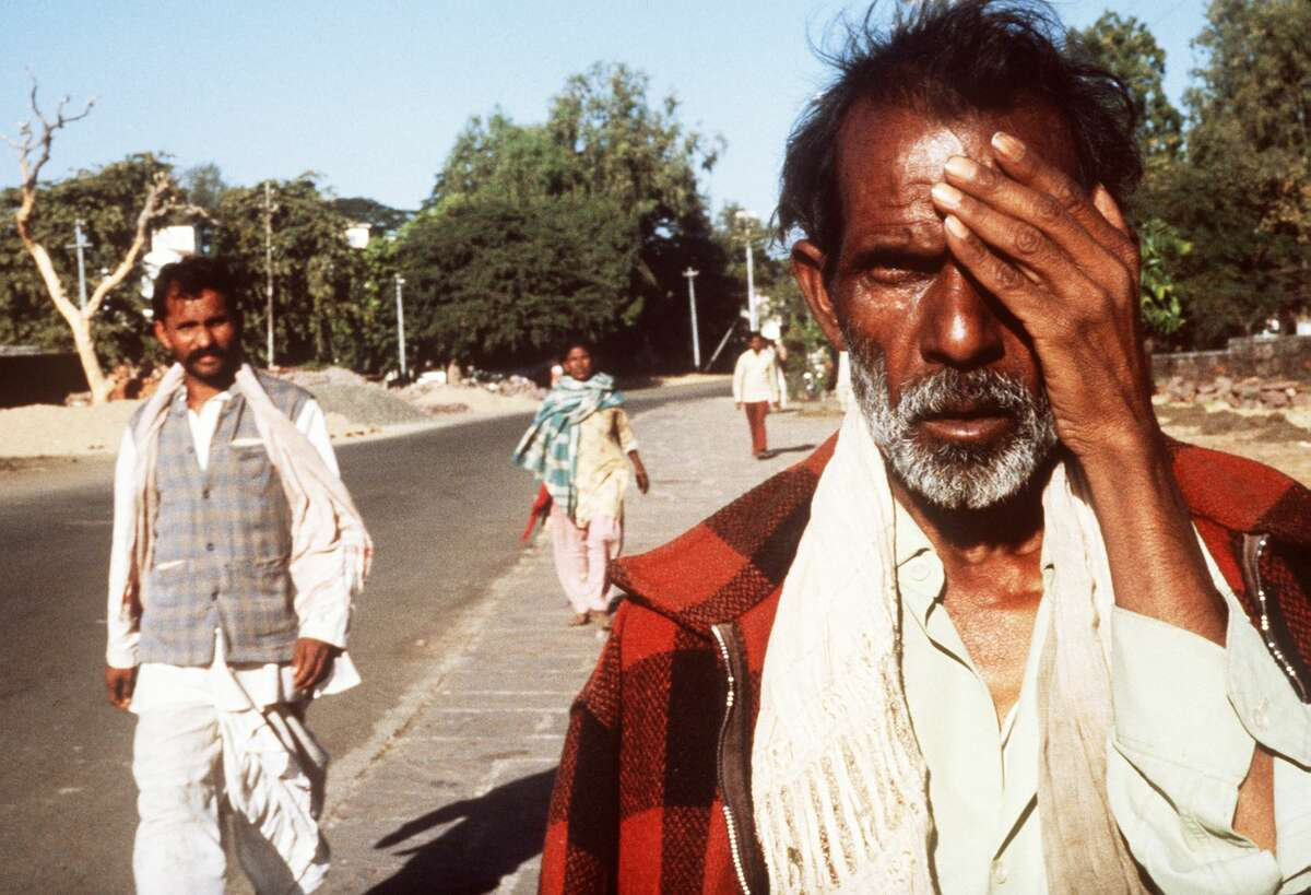 BHOPAL, INDIA - DECEMBER 4: Picture dated 04 December 1984, shows man victim of the Bhopal tragedy. A poison gas leak from the Union Carbide factory killed 2,500 persons and injured around 10,000. On background is the site of the factory. (Photo credit should read BEDI/AFP/Getty Images)