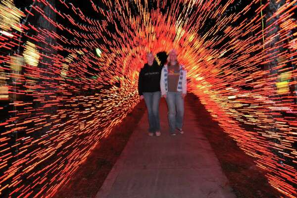 Bonnie Smiley, 14, and Elizabeth Ray, 17, enjoy walking through displays at a previous Dickinson Festival of Lights. The event, which features about 2 million Christmas lights, is scheduled through Dec. 30 at Paul Hopkins Park, 1000 FM 517 in Dickinson.