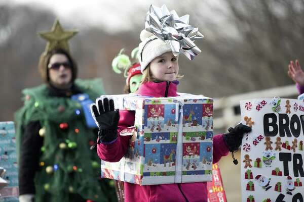 Eight-year-old Akaya Karlsen, of Waterbury, marches with Brownie Troop 60067, of Seymour, in the 45th annual Seymour Christmas Parade in downtown Seymour on Sunday.