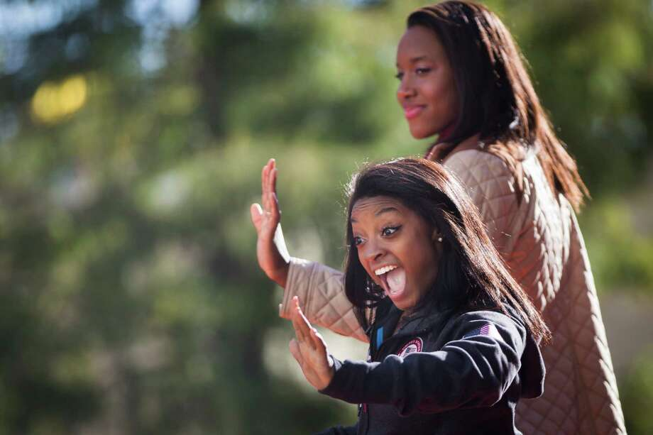 Gold Medalists Simone Biles, foreground, and Simone Manuel greet their fans at the 67th annual H-E-B Thanksgiving Day Parade. Photo: Marie D. De Jesus, Staff / © 2016 Houston Chronicle